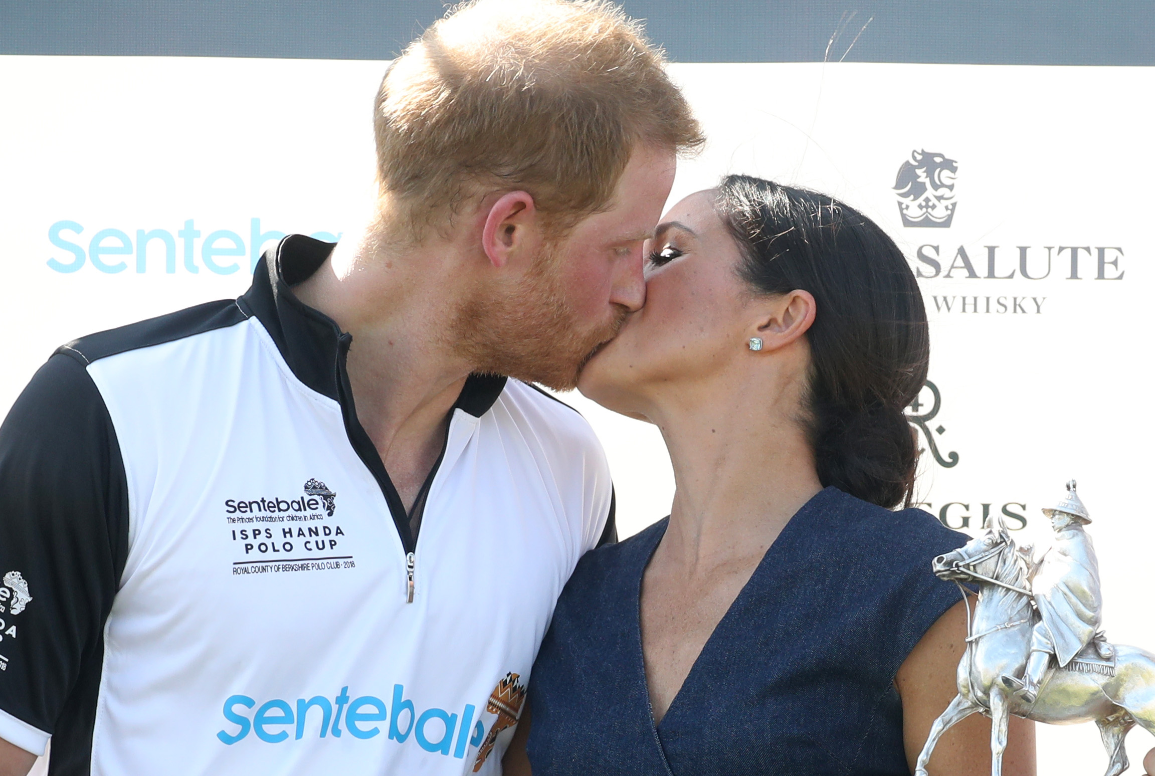 Meghan Duchess of Sussex and Prince Harry Duke of Sussex kiss after posing with the trophy after the Sentebale Polo 2018 held at the Royal County of Berkshire Polo Club on July 26, 2018, in Windsor, England. (Getty Images)
