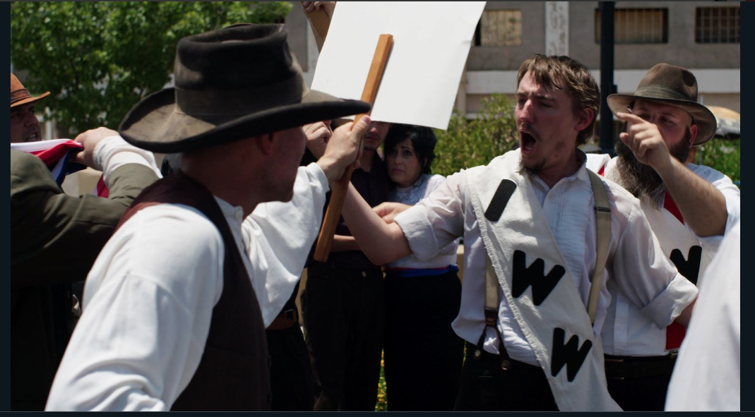 Townspeople playing the characters of striking miners from IWW protest on the streets of Bisbee, demanding safe working conditions.