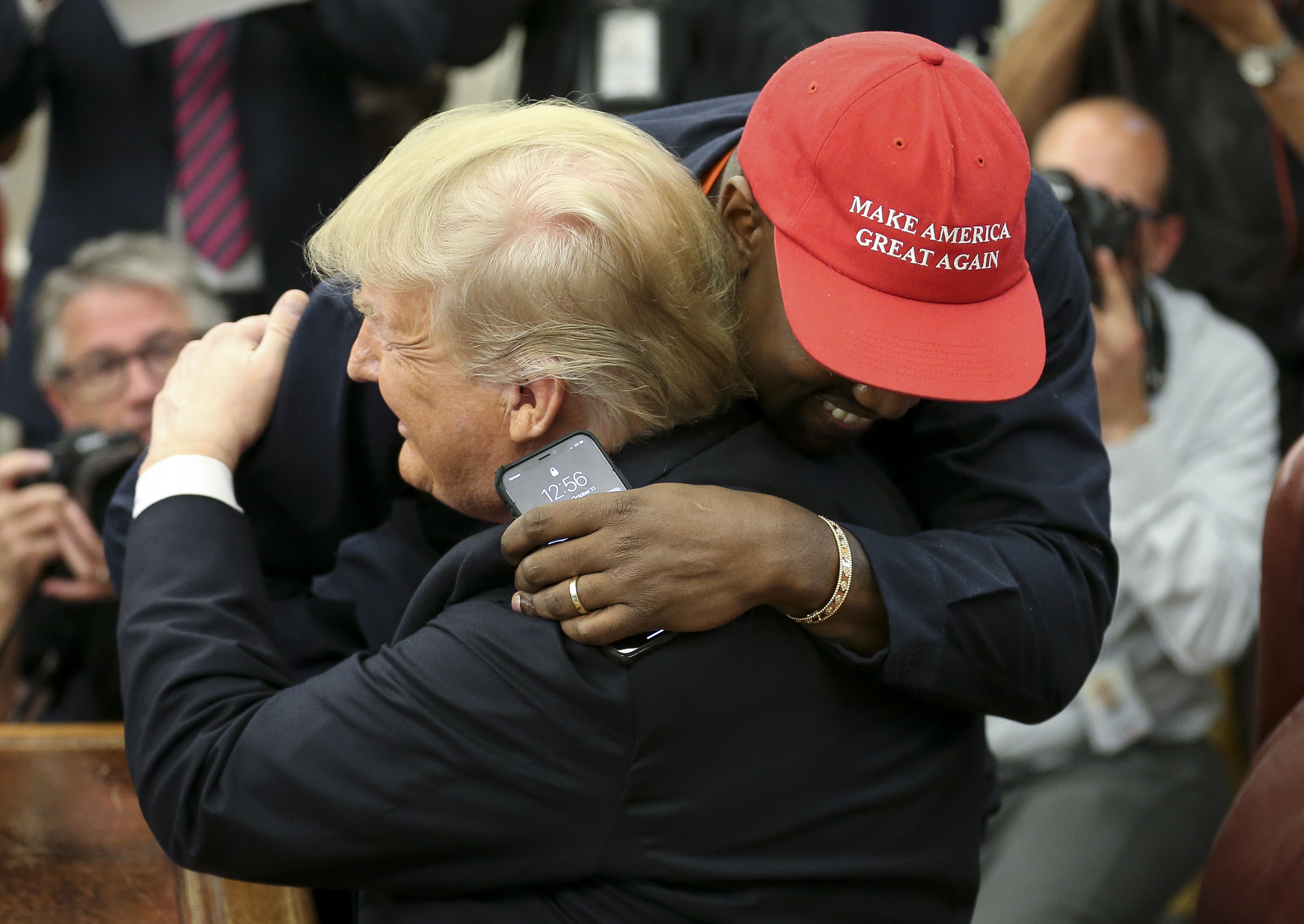 (AFP OUT) (EDITORS NOTE: Retransmission with alternate crop.) U.S. President Donald Trump hugs rapper Kanye West during a meeting in the Oval office of the White House on October 11, 2018 in Washington, DC.