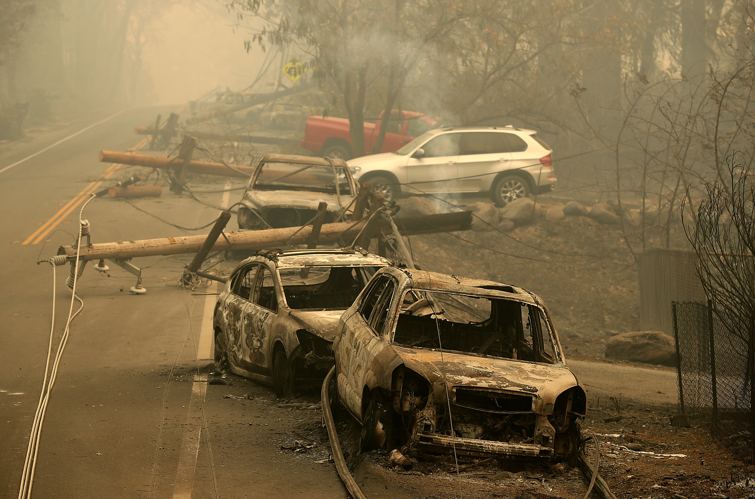 Power lines rest on cars that were burned by the Camp Fire on November 10, 2018, in Paradise, California. (Getty)